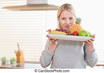 Woman holding a plate of fruits