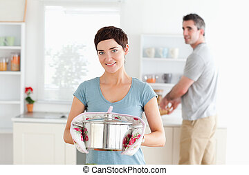 Woman holding a pot while man is washing the dishes