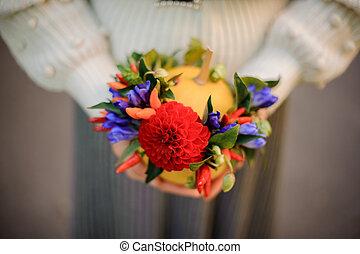 Woman holding a pumpkin decorated with red and blue flowers