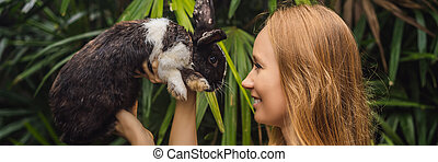 Woman holding a rabbit. Cosmetics test on rabbit animal. Cruelty free and stop animal abuse concept BANNER, LONG FORMAT