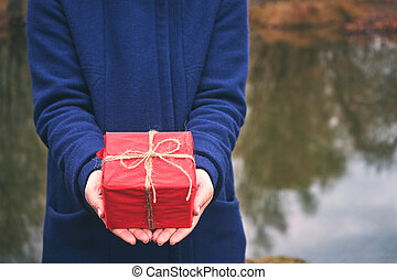 Woman holding a red box gift in forest, winter day