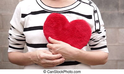 Woman Holding a Red Fuzzy Heart - Close up shot of an...