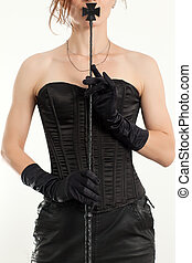 Woman in black corset on a gray background holds a riding crop