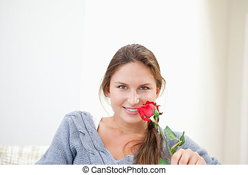 Woman holding a rose while smiling
