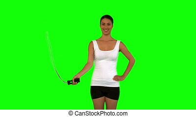 Woman holding a skipping rope against a green screen