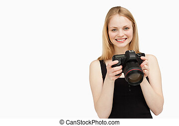 Woman holding a SLR camera while smiling against white...