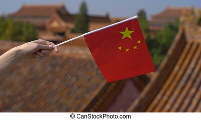 Woman holding a small flag of China in her hands. Travel to...
