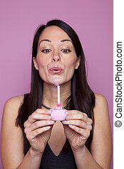 Woman holding a small pink birthday cake