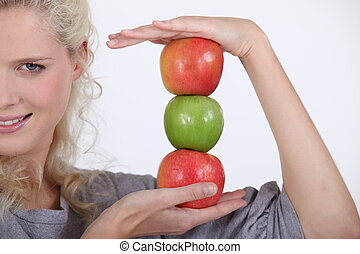 Woman holding a stack of apples