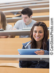 Woman holding a tablet pc while smiling in lecture hall