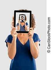 Woman holding a tablet showing a picture of herself