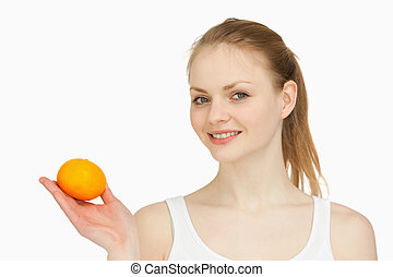 Woman holding a tangerine in her hand against white...