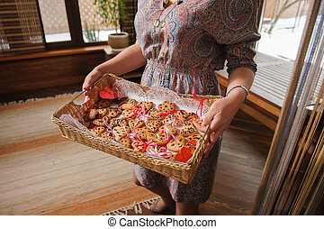 woman holding a tray with cookies in form of heart