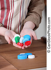 Woman holding a variety of plastic bottle caps