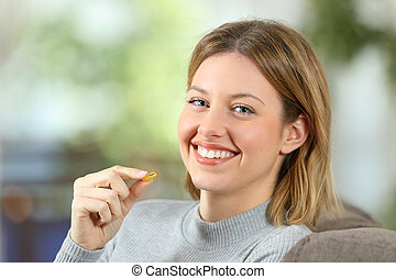 Woman holding a vitamin pill and looking at camera