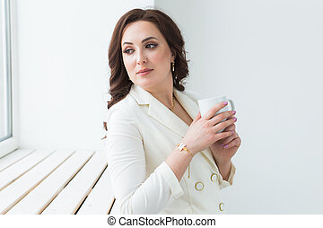 Woman holding a white cup of coffee. With a beautiful manicure. Drink, fashion, morning