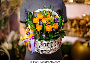 Woman holding a wicker basket with flowers