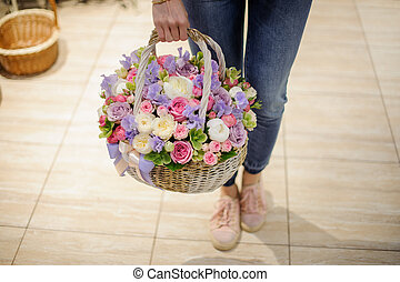 Woman holding a wicker basket with tender flower composition consisting of pink and purple roses, ranunculus and other flowers