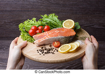 Woman holding a wooden plank with raw salmon. Raw salmon steaks on wooden board. Lettuce leaves, spices, lemon slices on a wooden board. Woody background. view from above. Hands of a woman in frame