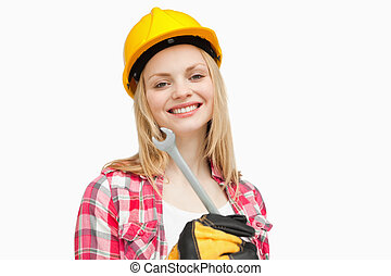 Woman holding a wrench while smiling