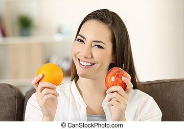 Woman holding an apple and orange looking at camera
