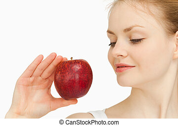 Woman holding an apple while looking at it