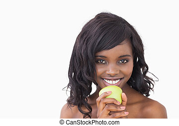 Woman holding an apple while smiling