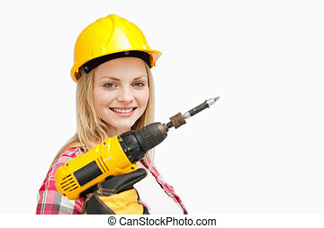 Woman holding an electric screwdriver while smiling