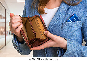 Woman holding an empty wallet in shopping centre