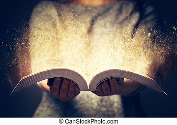 Woman holding an open book bursting with light.