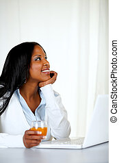Woman holding an orange juice and looking up