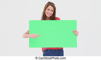 Woman holding and pointing a blank poster against white...