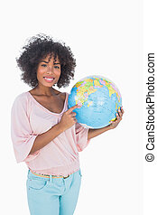Woman holding and pointing to globe