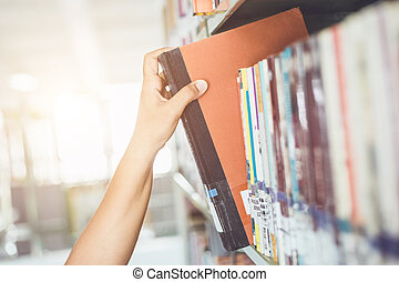 Woman holding and reading book in the public library room....