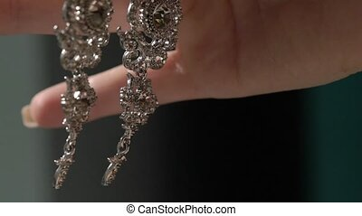 Woman holding and touching earrings - Woman holding and...