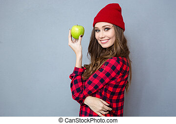 Woman holding apple and looking at camera