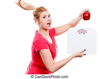 Woman holding apple and weight machine