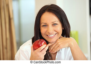 Woman holding apple with bright smile
