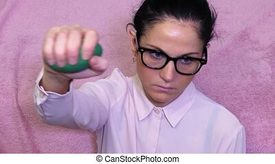 Woman holding arm up and squeezing green stress ball