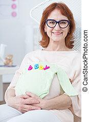Woman holding baby bodysuit