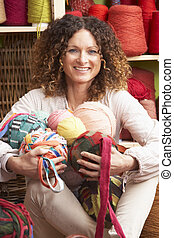 Woman Holding Balls Of Wool Sitting In Front Of Yarn Display