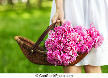 Woman holding basket of peony in her hand