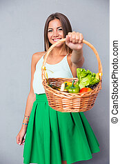 Woman holding basket with vegetables - Portrait of a happy ...
