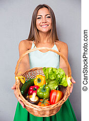 Woman holding basket with vegetables - Portrait of a pretty ...