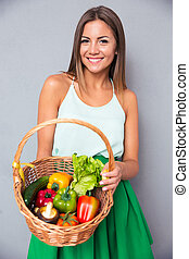 Woman holding basket with vegetables - Portrait of a smiling...