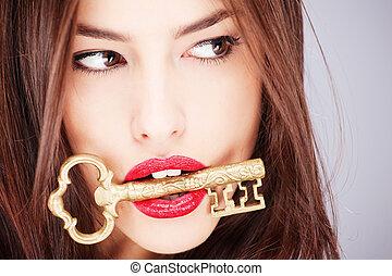 woman holding big old key - Pretty woman holding big old key...