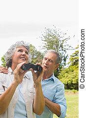 Woman holding binoculars with partner