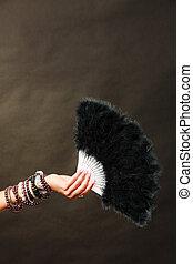 woman holding black feather fan in hand