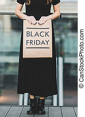 Woman holding Black Friday paper bag
