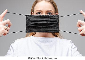 Woman holding black respirator in hands. Corona virus protection concept.